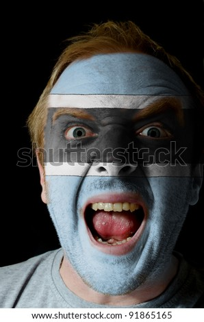 Low key portrait of an angry man whose face is painted in colors of botstwana flag
