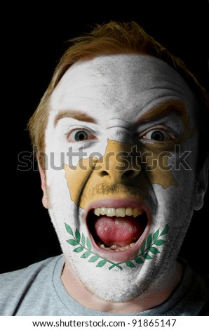 Low key portrait of an angry man whose face is painted in colors of Cyprus flag