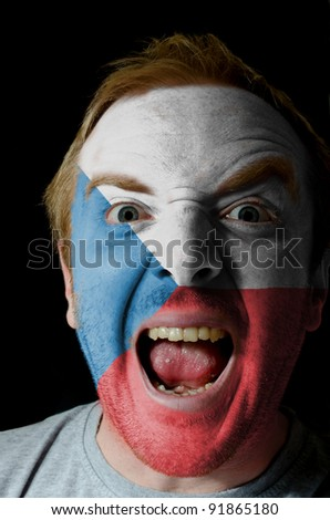 Low key portrait of an angry man whose face is painted in colors of czech flag
