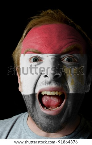 Low key portrait of an angry man whose face is painted in colors of egypt flag
