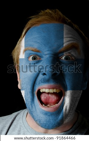 Low key portrait of an angry man whose face is painted in colors of finland flag