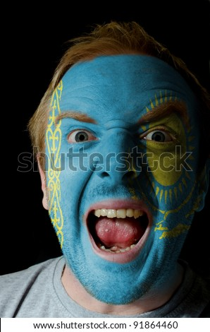 Low key portrait of an angry man whose face is painted in colors of kazakstan flag