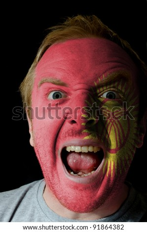 Low key portrait of an angry man whose face is painted in colors of kyrghyzstan flag