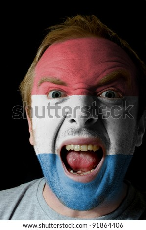 Low key portrait of an angry man whose face is painted in colors of netherlands flag