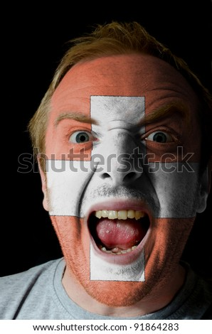 Low key portrait of an angry man whose face is painted in colors of swiss flag