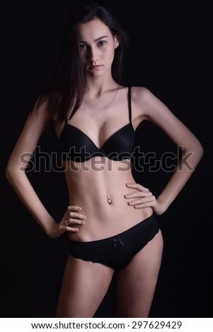 low key portrait of beautiful woman in black underwear over dark background - stock photo