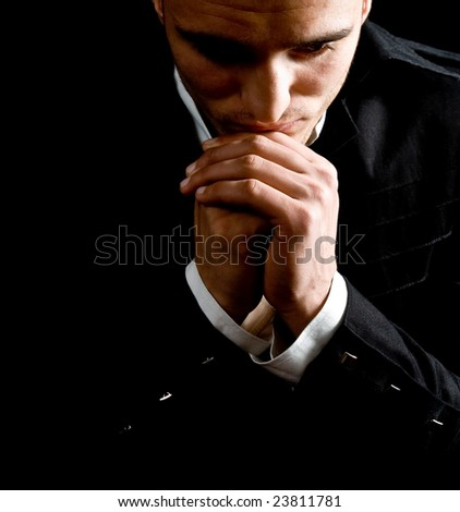 Low-key portrait of businessman praying for success - stock photo