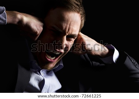 Low-key portrait of desperate businessman in dark suit screaming and holding both fists at head expressing strong despair, isolated on black background. - stock photo
