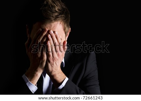Low-key portrait of desperate office manager in dark suit covering his face with both hands, isolated on black background with copy-space. - stock photo
