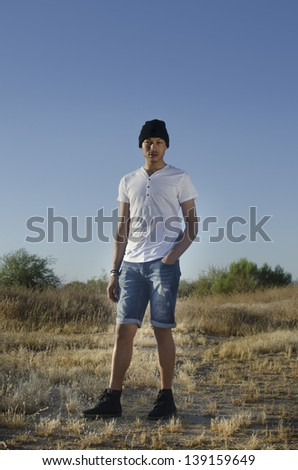 Low key portrait of male model wearing casual clothing and baseball cap - stock photo