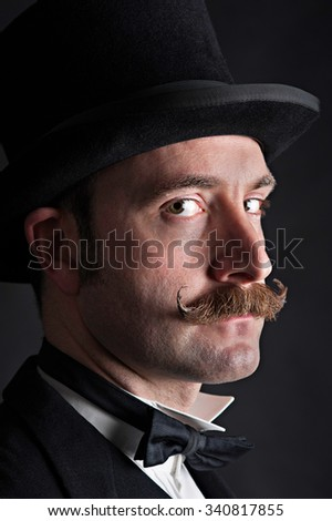 Low key portrait of male wearing a black top hat. He has a moustache and is looking sideways on into the camera. He has a straight expression on his face. He could be a magician or Victorian gent. - stock photo