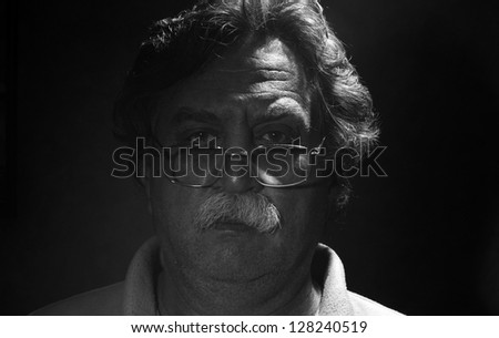 low key portrait of  middle-aged man, black and white - stock photo