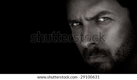 Low-key portrait of scary man with evil eyes - stock photo
