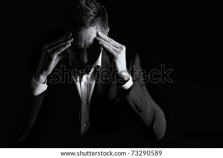 Low-key portrait of worried business person in dark suit sitting at office desk looking down and contemplating with both hands resting at head, black & white conversion. - stock photo