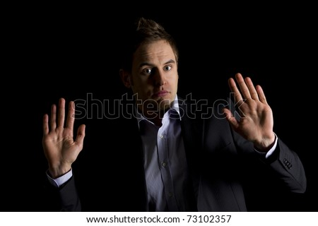 Low-key portrait of young clueless business person in dark suit sitting at office desk being confused, isolated on black background with copy-space. - stock photo