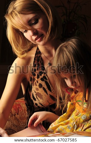 Low key portrait of young mother reading a book for her child . - stock photo