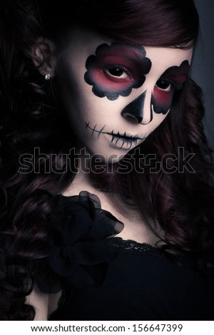 Low key portrait of young woman with sugar skull make-up. - stock photo