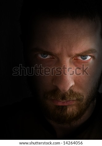 Low-key portrait - sad and angry looking man - stock photo
