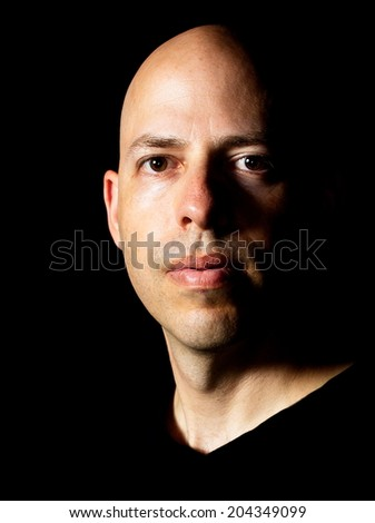 Low-key Rembrandt lighting portrait of a 40 year old bald man on black background