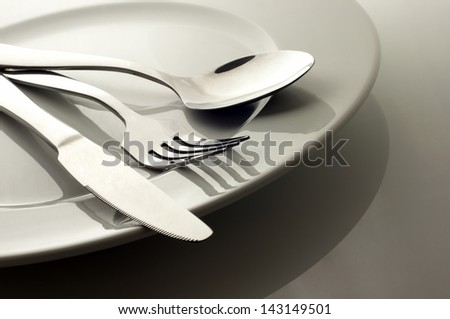 Low key shot-forks and knives on plate - stock photo