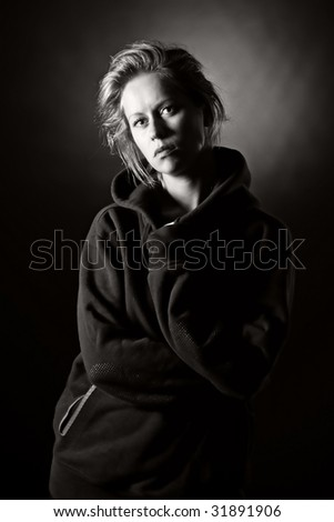 Low Key Shot of a Blonde Girl in Hooded Top - stock photo