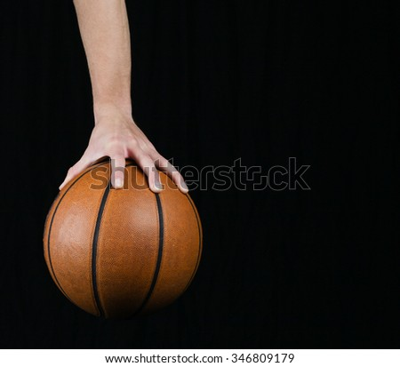 Low key shot of a hand holding a basket ball - stock photo