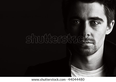 Low Key Shot of a Handsome Male against a Dark Background - stock photo