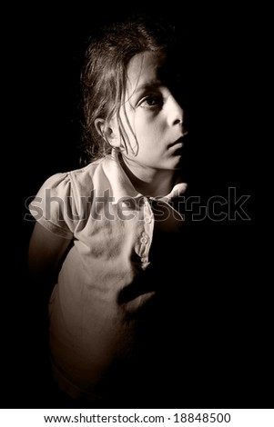 Low Key Shot of a Young Child Looking Off Camera with Lighting from the side - stock photo