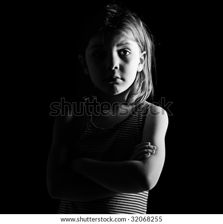 Low Key Shot of a Young Child with her Arms Crossed - stock photo