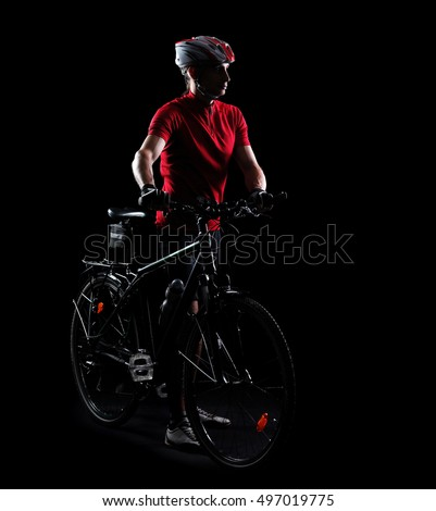 Low key side view silhouette of a mountain biker with his bicycle in a black studio