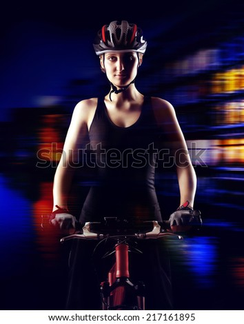 low key silhouette of a girl cyclist  with her bicycle on city lights background - stock photo