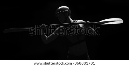 Low key studio lighting on whitewater kayaker holding his paddle - stock photo
