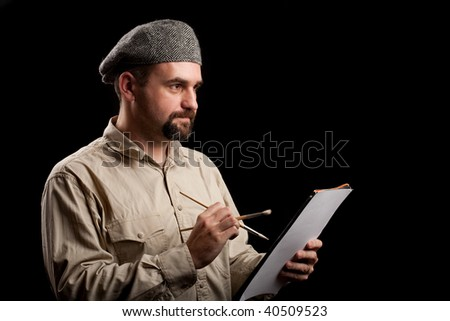 Low key studio portrait of a painter with hat, holding brushes and easel - stock photo