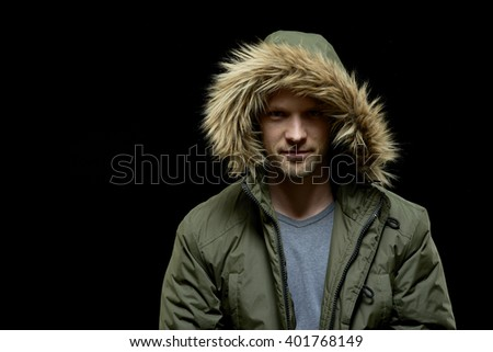 Low key studio portrait of young adult confident caucasian model wearing winter coat with hood on and smirking. Isolated on black. - stock photo