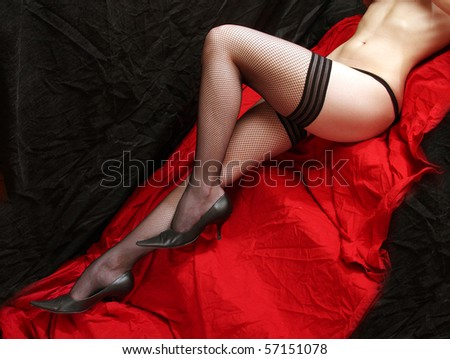 Low key studio shot beautiful slim legs in black net nylons on a red background. Great image for calendar. - stock photo