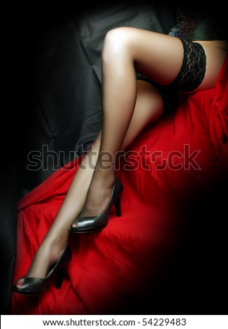 Low key studio shot beautiful slim legs in black nylons on a red background. Great image for calendar. - stock photo