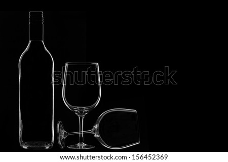 Low-key Studio Shot of a Wine Bottle and Two Wine Glasses on a Black Background.Copy Space.  - stock photo