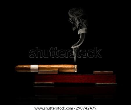 Low key studio shot of fine cigar burning in elegant ashtray with visible smoke on black background - stock photo