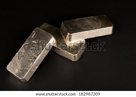 Low key take of sterling silver bars on a black background - stock photo