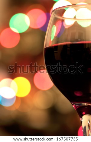 Low light image of Glass of red wine against colorful Christmas bokeh lights background
