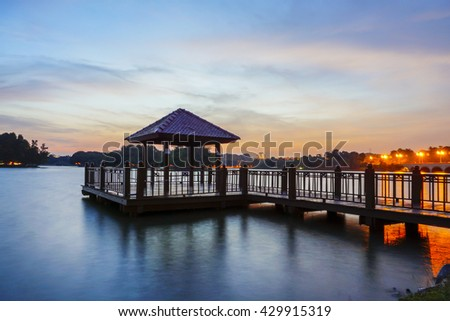 Low light long exposure scenery of a lake with wooden observation jetty in blue hour, with motion blur effects on surface of water and sky. - stock photo