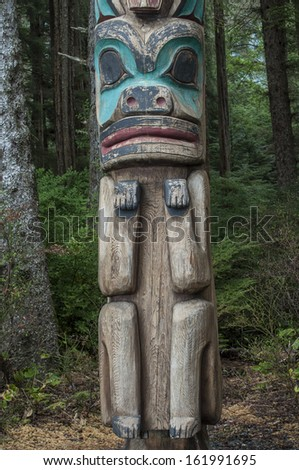 Low man on a wooden cedar Tlingit totem pole in a pine forest in Sitka, Alaska - stock photo