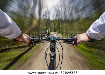 Low perspective of a bike riding fast through the forrest - stock photo
