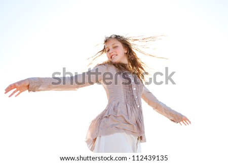 Low perspective of a young girl flicking her wet hair in the air, smiling against the sky. - stock photo