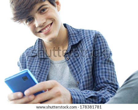 Low perspective portrait view of a joyful teenager boy sitting down against a sunny sky using his smartphone mobile joyfully smiling. Lifestyle technology. - stock photo