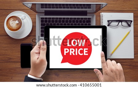 LOW PRICE, on the tablet pc screen held by businessman hands - online, top view - stock photo