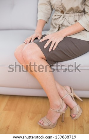 Low section of a beautiful well dressed young woman sitting on sofa at home