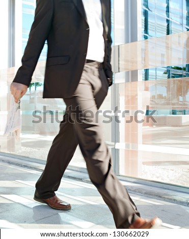 Low section of a businessman walking passed a modern glass office building in the city, carrying a financial newspaper in his hand. - stock photo