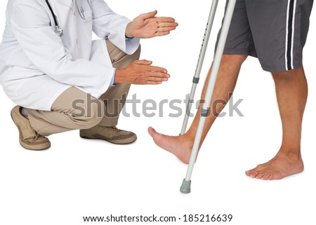 Low section of a doctor with senior man using walker over white background - stock photo