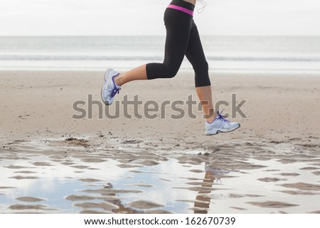 Low section of a healthy young woman jogging on shore at beach - stock photo